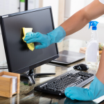 Person in disposable gloves cleaning a desktop screen with a cleaning cloth
