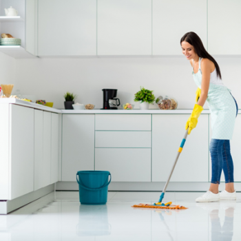 Woman cleaning kitchen floor with a mop and bucket