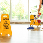 Person cleaning workplace floor with a mop, bucket and a wet floor sign