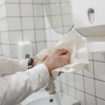 Person drying their hands with paper hand towels