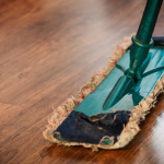 Mop being used to clean a wooden floor
