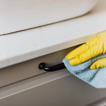 Person using a microfibre cloth to clean cupboard door handles